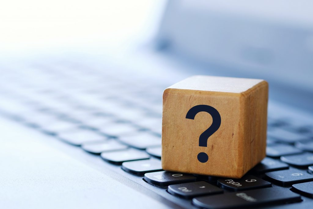 A question mark on a wooden cube on a computer keyboard, with a blurred background and shallow depth of field.
